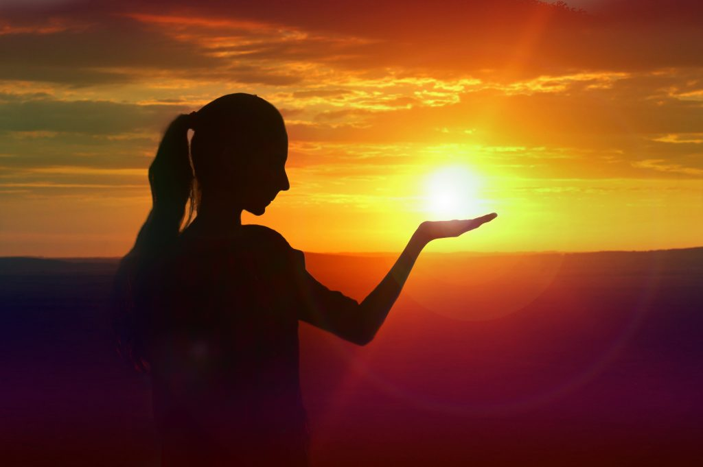 Optical illusion of a girl holding the sun during sunset.