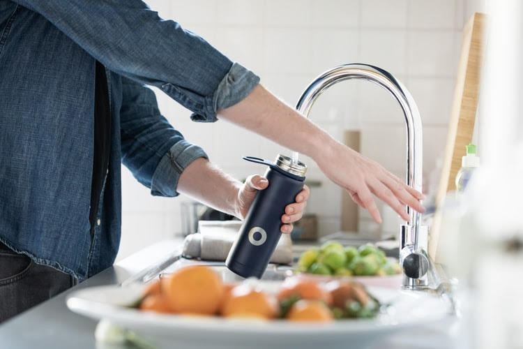picture of a person filling water from a faucet