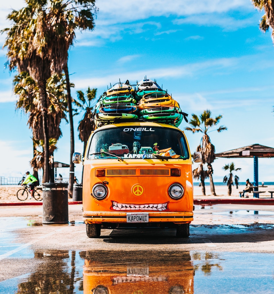 Image of a camper van with surf boards stacked on top in Hawaii