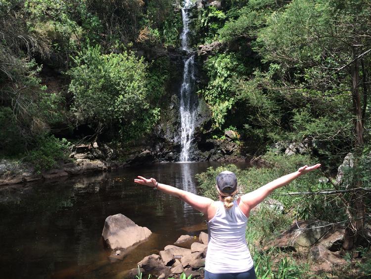 Woman in front of a hawaiian waterfall on the hamakua coast of the Big Island